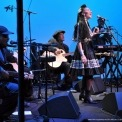 Woman wearing a black dress singing into a microphone while playing a percussion instrument with five other people in black playing instruments around her in front of a blue background.