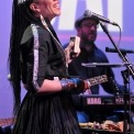 Woman wearing a black dress singing into a microphone while playing a percussion instrument and a man in black playing the keyboard behind her all in front of a purple background.