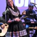 Woman wearing a black dress and smiling while playing a percussion instrument and a man in black playing the keyboard behind her all in front of a purple background.