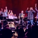 6 people singing and 3 people seen playing instruments behind them. Everyone is on a sage in front of a red background.