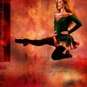 A woman in a green dress and black tights Irish dancing in front of an orange background.
