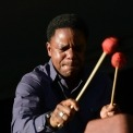 An African American man holds two drumsticks with red ends in front of a black background with his eyes closed.