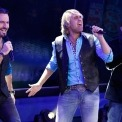 Three men stand singing into microphones wearing jeans, black vests, and blue button downs. The man on the right has on a white shirt and blue suit jacket.