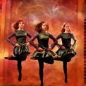 Three women Irish dancing in green dresses and black tights in front of an orange background.