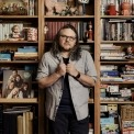 Jeff Tweedy standing in front of a bookcase.