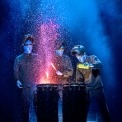 Three bald blue man standing in front of two drums pouring paint onto them in front of a blue and black background