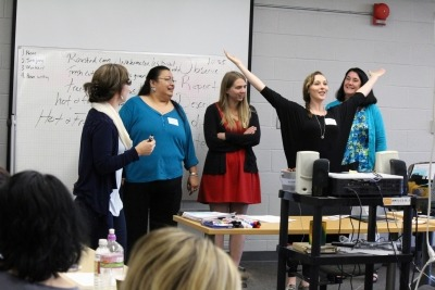 Image of five teachers standing at the front of a classroom and one teacher has her arms raised wide above her head.