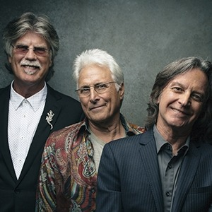 All three members of the Nitty Gritty Dirt band standing in a line in front of a gray background
