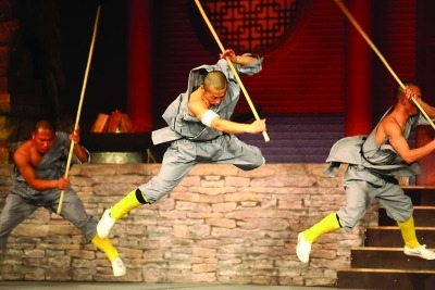 Man in grey costume performing Martial Arts with a Rattan stick