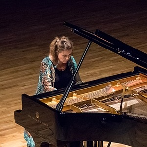Image of Gabriela Monteri, taken from an elevated position, showing her seated at a piano in a colorful robe.