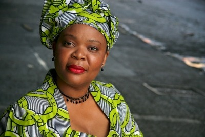 African women wearing a green, grey, and black head scarf. Her shirt matches the head scarf. She has red lipstick on and is wearing a black necklace and black earrings.