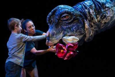 Image of a young boy and a performer from Erth's Dino Zoo on stage feeding flowers to a brachiosaurus.