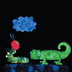 Image of the caterpillar and green chameleon puppets from The Very Hungry Caterpillar and Other Eric Carle Favorites looking at a blue cloud with a black background