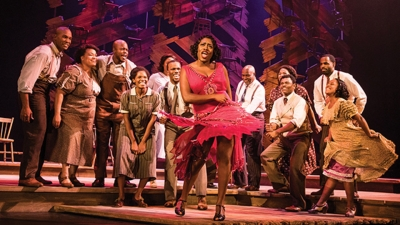 Image of a cast member dancing in a red dress while other cast watch