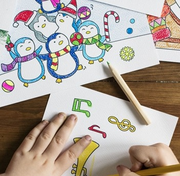 Image of two hands coloring a drawing with a yellow color pencil and an additional completed coloring pages on the table