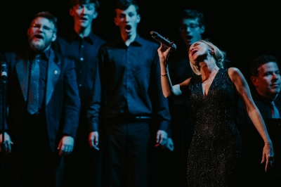 Image of Kristin Chenoweth on the Lied Center stage in a black dress singing powerfully into a microphone with the chorus standing behind her.