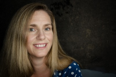 Photo of Jana Eggers in a blue shirt against a dark background.