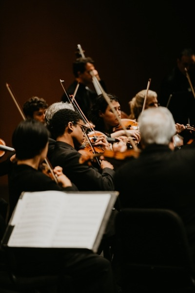 Image of the Orpheus Chamber Orchestra performing at the Lied Center with a music stand in the foreground and the string section in the background.
