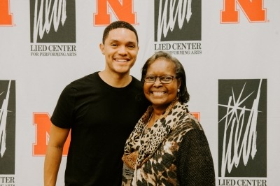 Image of Trevor Noah posing with a Lied Center donor in front of the white backdrop with red University of Nebraska logos and black Lied Center logos.
