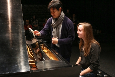 Image of Yekwon Sunwoo standing by a piano and pointing to the sheet music in front of a UNL student seated at the piano during a master class.