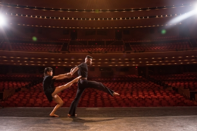 Image of two dancers dressed in black on the Lied Center stage looking out toward an empty auditorium