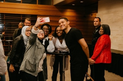 Image of Trevor Noah taking a selfie with fans