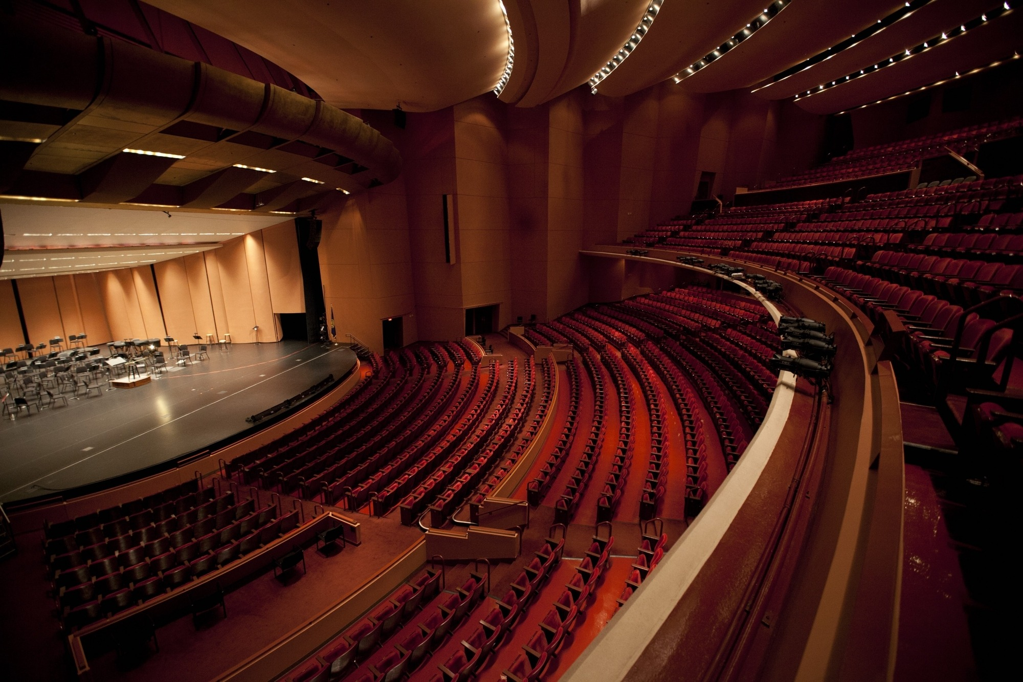 Image of the empty Lied Center auditorium taken from the corner of the balcony showing the orchestra shell and music stands on stage