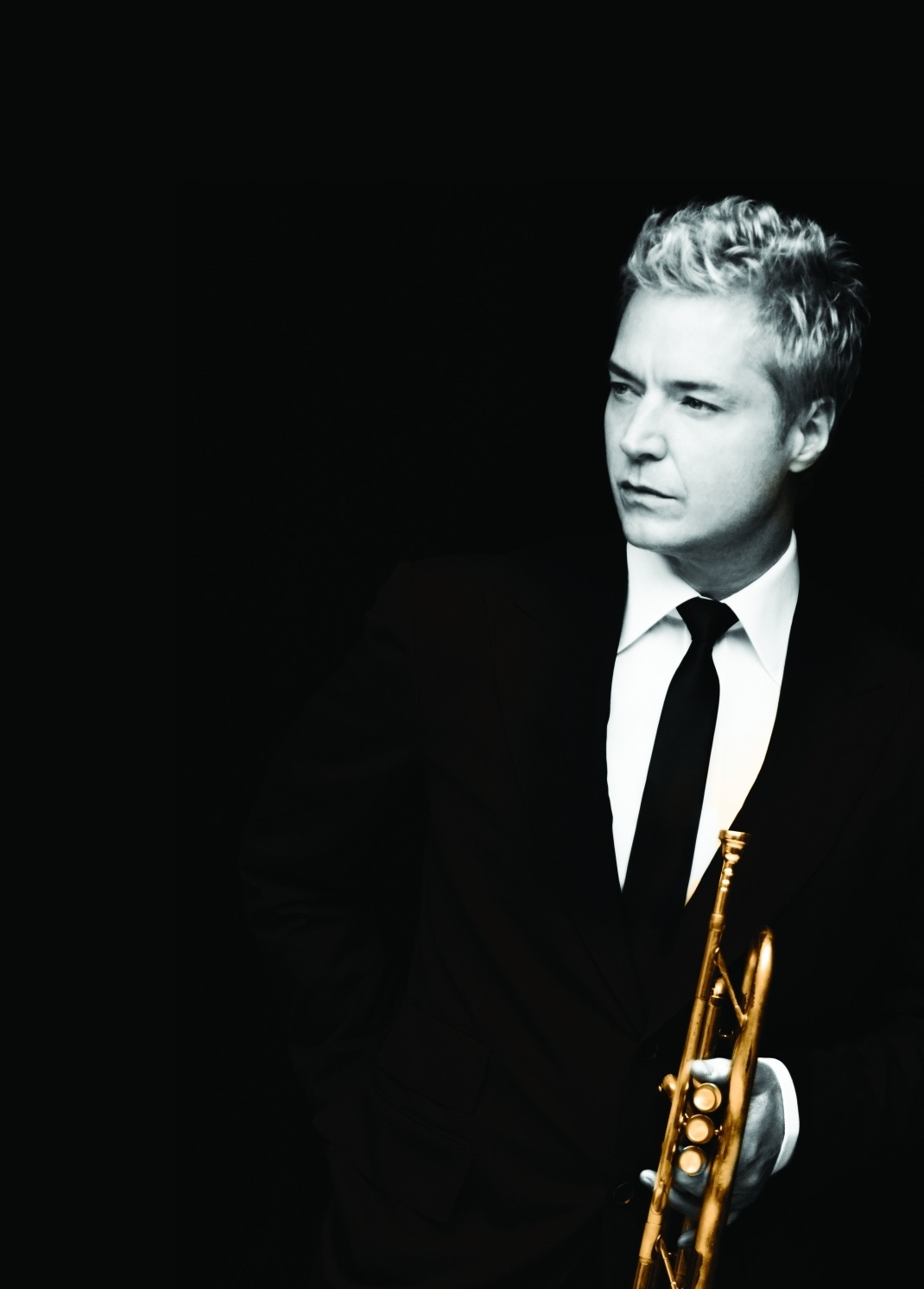 Black and white image of trumpet player Chris Botti wearing a suit and tie.