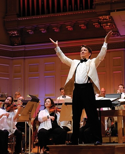 Image of Keith Lockhart on stage with arms raised facing the audience with the Boston Pops in background