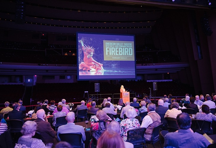 Image of Shelby Fenster at the podium in front of a projection screen speaking to a large audience during the Lied Center On Stage donor event