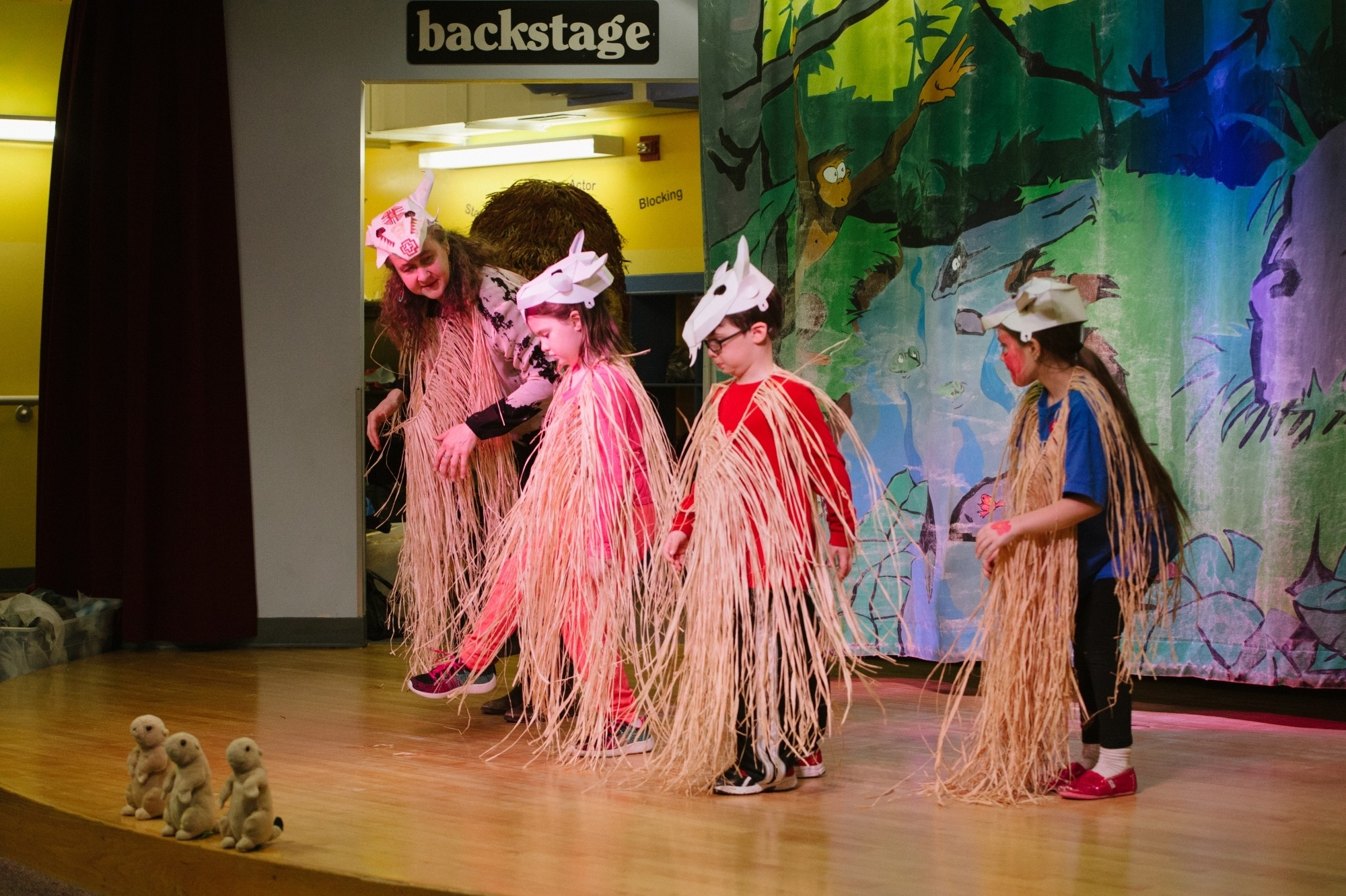 Image of three children on stage with Heather Henson wearing grass outfits and paper hats shaped like animal skulls