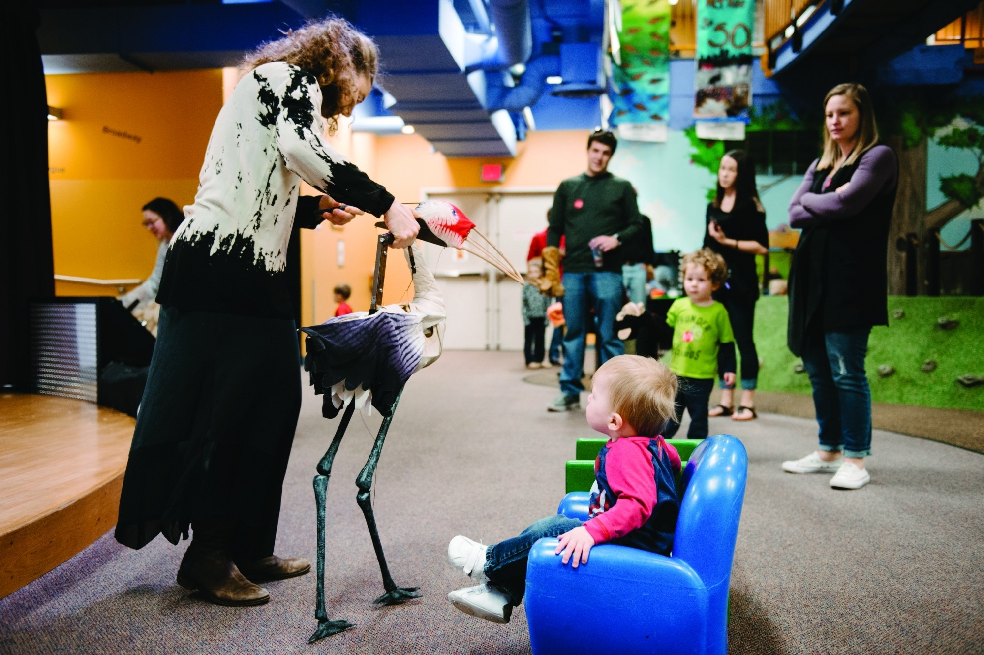 Image of a toddler sitting in a small blue chair that the Lincoln Children's Museum watching Heather Henson demonstrate walking the crane puppet from Crane: On Earth, In Sky