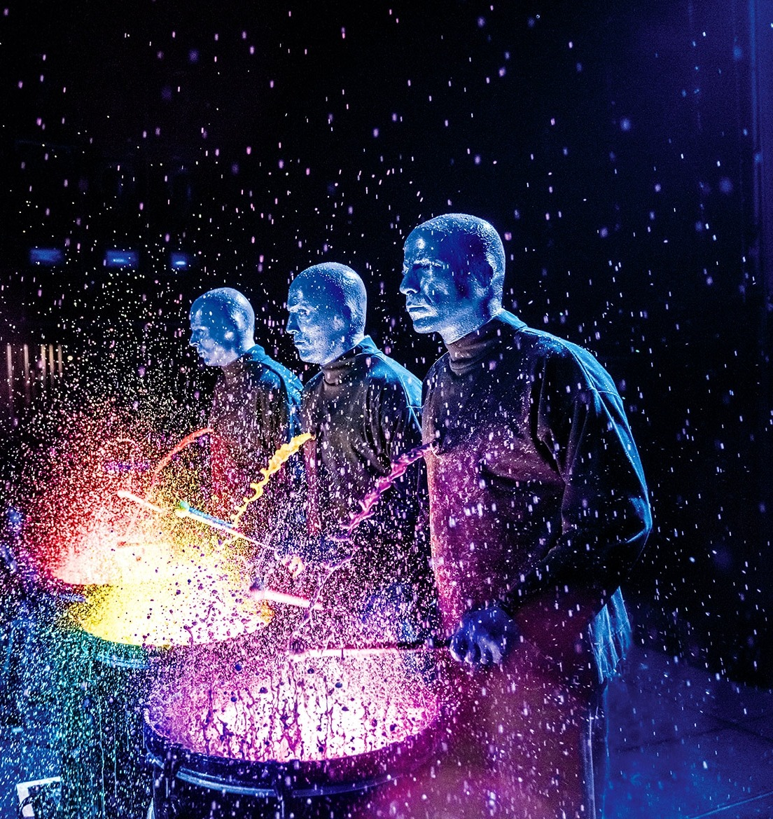 Blue Man Group playing paint drums