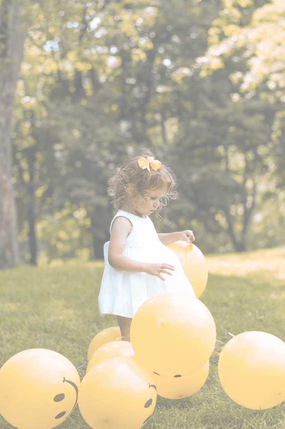 Image of a young girl in a white dress playing with yellow smiley-face balloons in the green grass