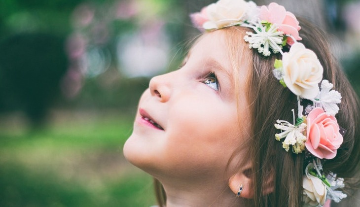 Image of a young girl wearing a crown of peach and yellow flowers looking up to the sky.