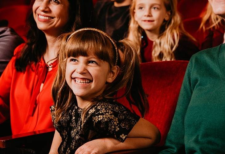 Image of a smiling little girl in the audience enjoying a show at the Lied Center