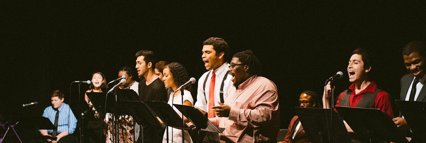 Image of the performers of Gumbo standing at microphones in front of music stands during the ASCAP Grow a Show staged reading