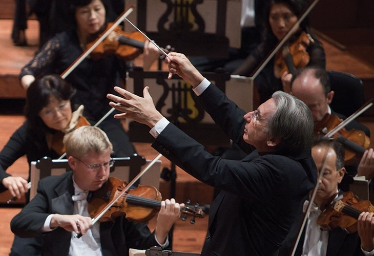 Image of the conductor of The San Francisco Symphony gesturing with his baton with the string section in the background