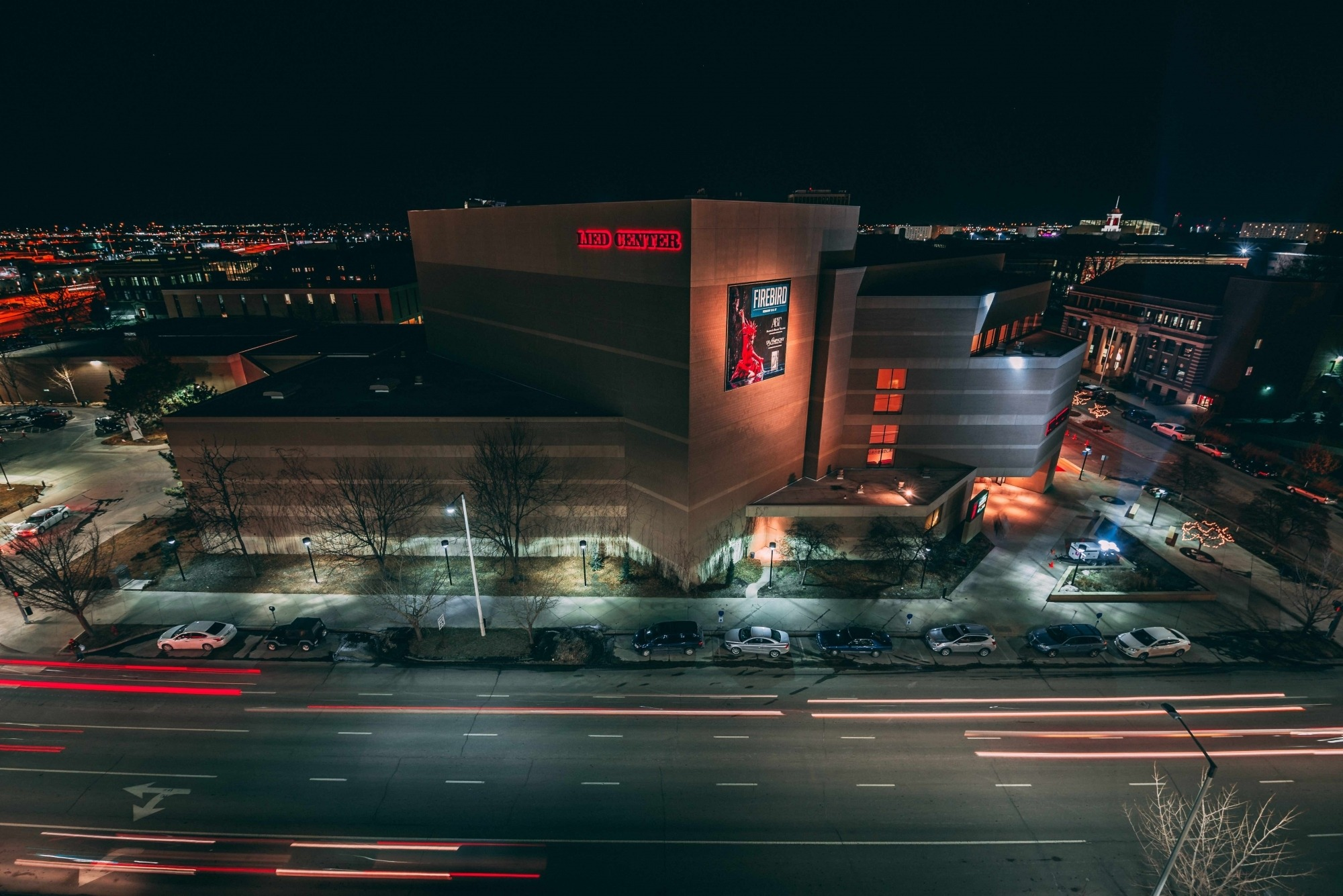 Image of the Lied Center building at night taken from the roof of a nearby building showing searchlights pointed towards the sky and car lights streaking across the road