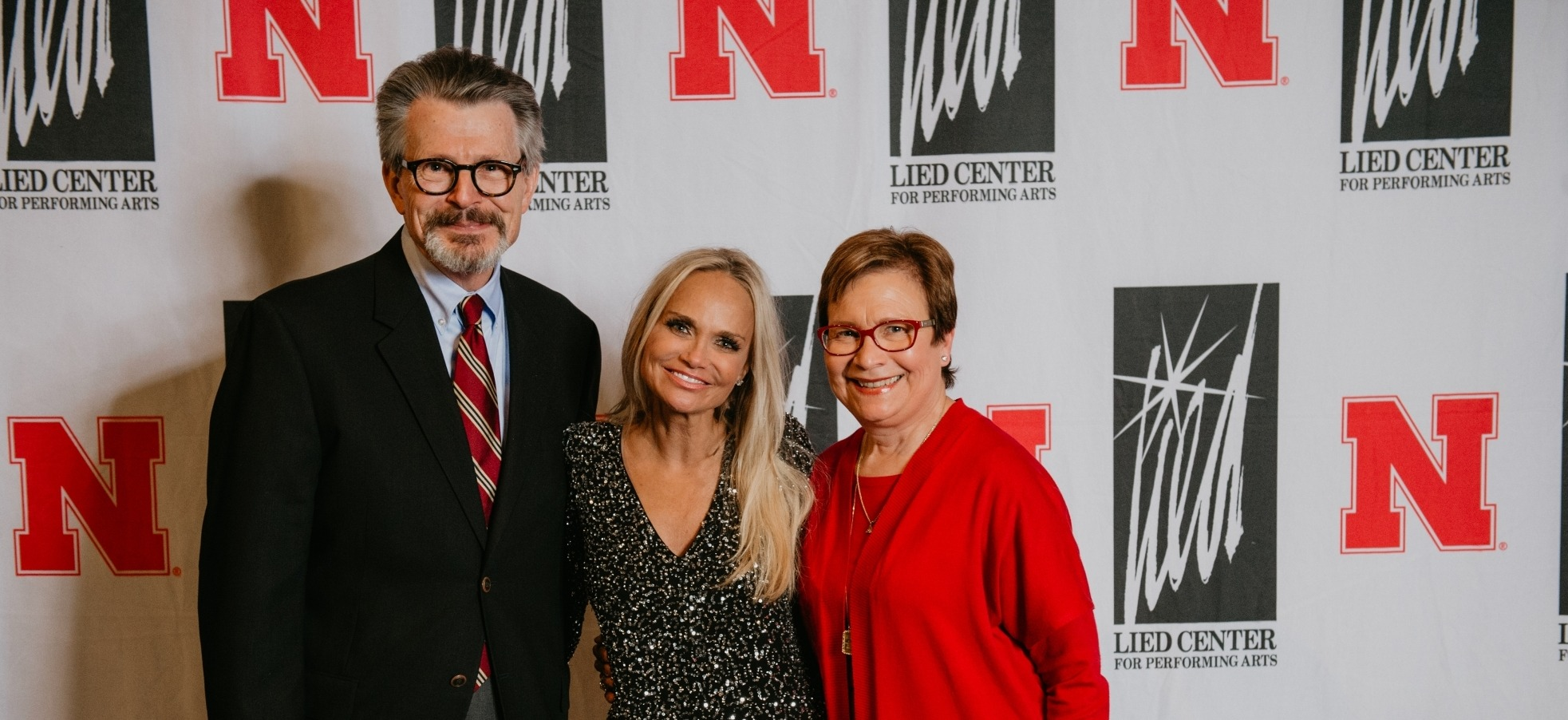 Photo of Kristin Chenoweth wearing a silver dress taking a meet and greet photo in front of a step and repeat backdrop with Nebraska and Lied Center logos.