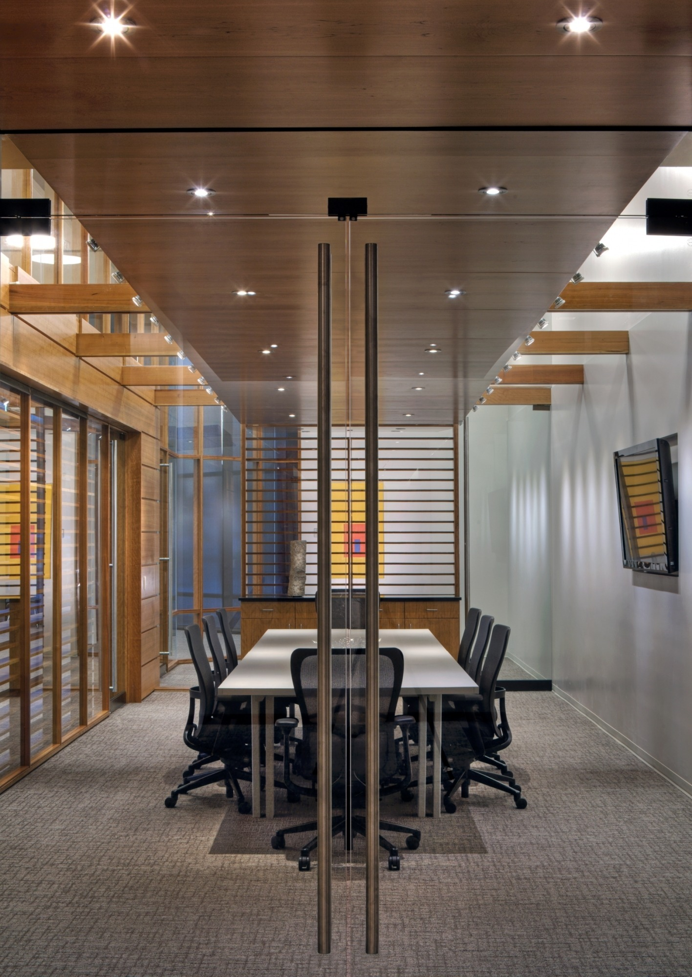 Image of the Lied Commons Boardroom taken through the glass doors showing the long table and a TV on the wall.