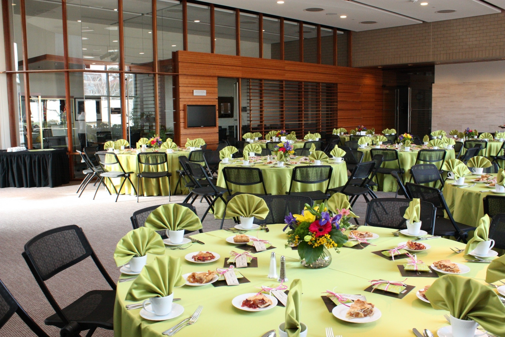 Image of the Lied Commons setup for a luncheon featuring round tables with light green linens and colorful centerpieces.