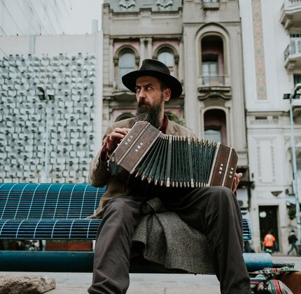 Image of a man with a black and grey beard wearing a black hat sitting on a public bench playing the accordion.