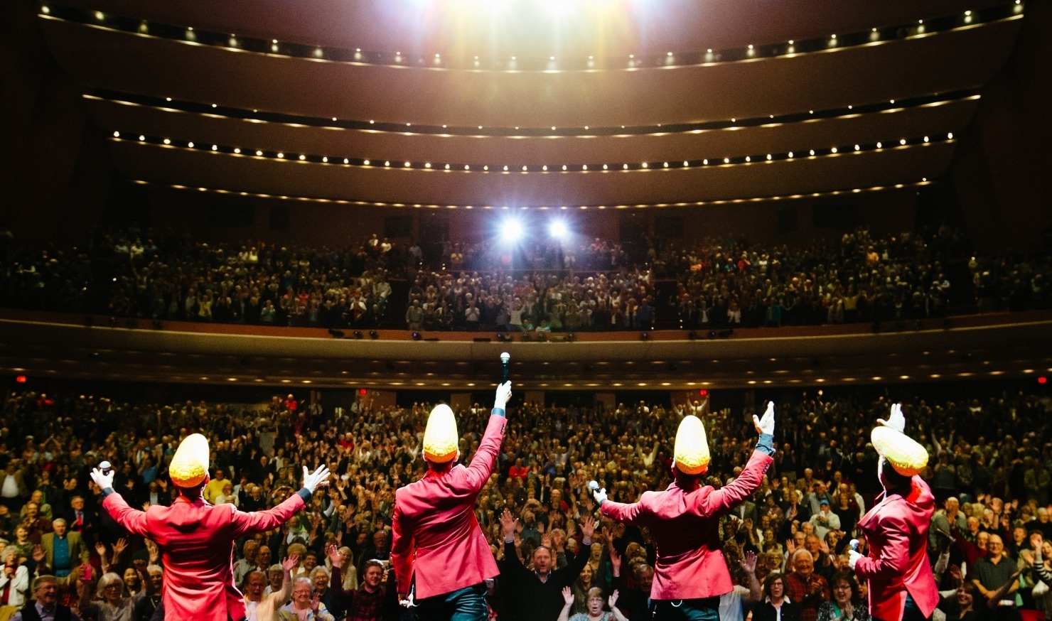 Midtown Men performing in red suit jackets with cornhead hats at the Lied Center for a packed crowd.
