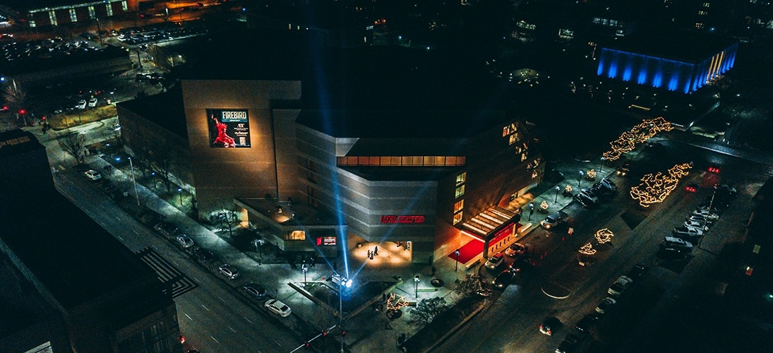 Image of the Lied Center building at night with searchlights shining taken from the roof of a tall adjacent building
