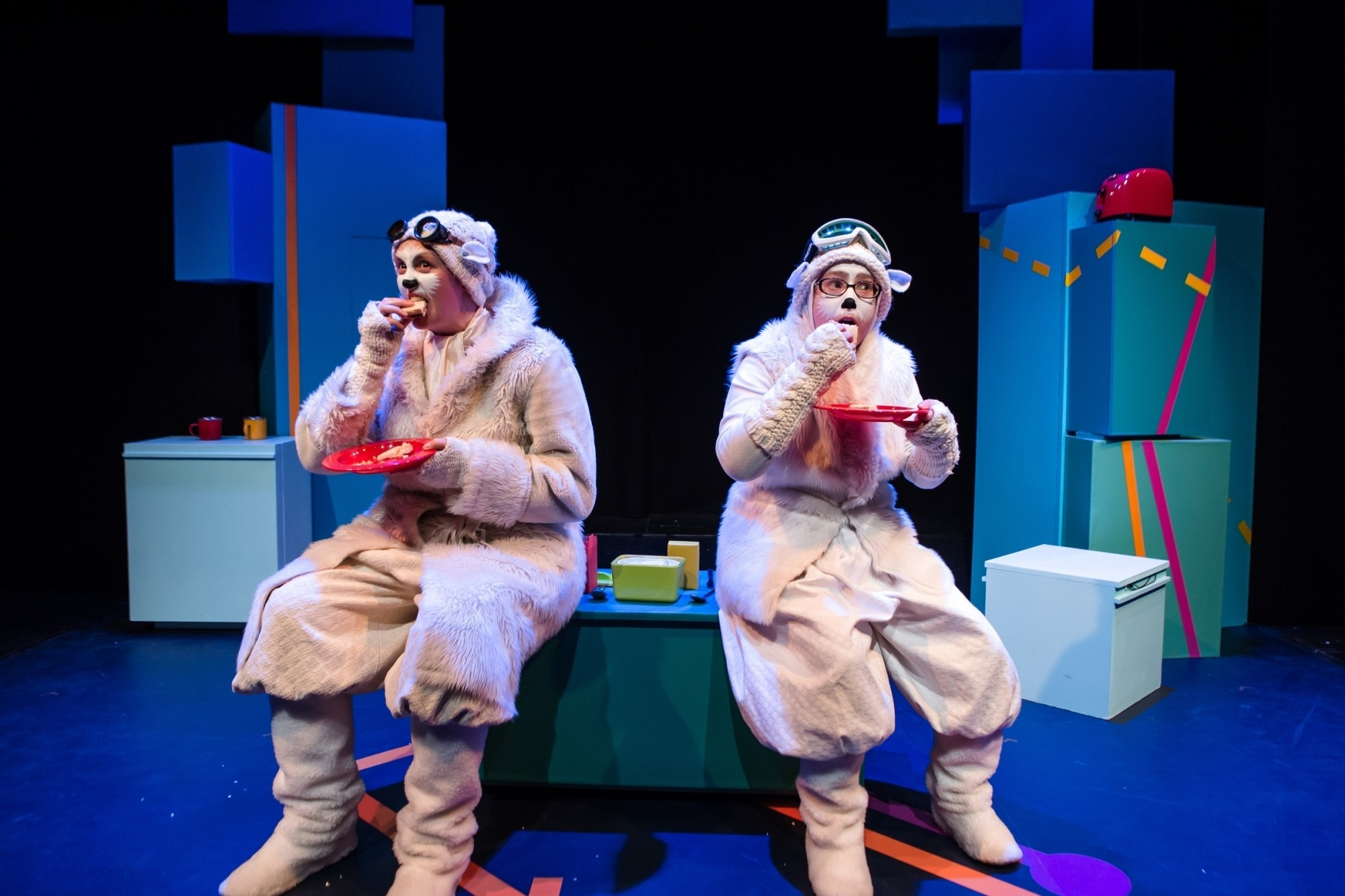 Image of two characters from The Polar Bear Goes Up dressed in polar bear costumes eating sandwiches off of red plates while sitting on a blue set