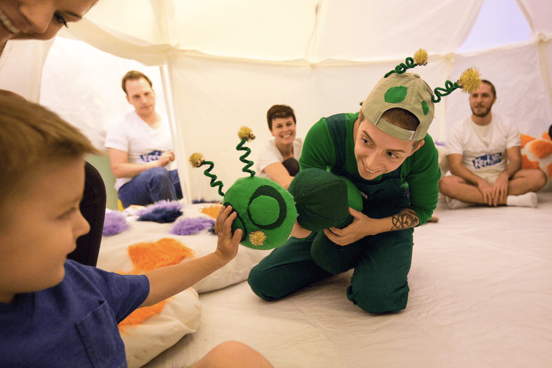 Image of performer in a green costume from A Very Hungry Caterpillar introducing the caterpillar puppet to a young boy.