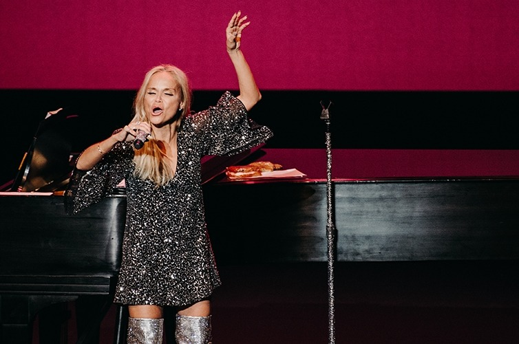 Image of Kristin Chenoweth on stage in front of a piano with arm raised singing during her Lied Center performance