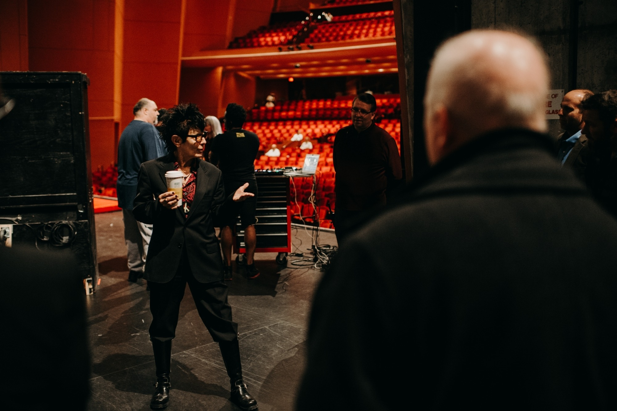 Elizabeth Streb wearing a black suit holding a cup of coffee gesturing to a group of people.