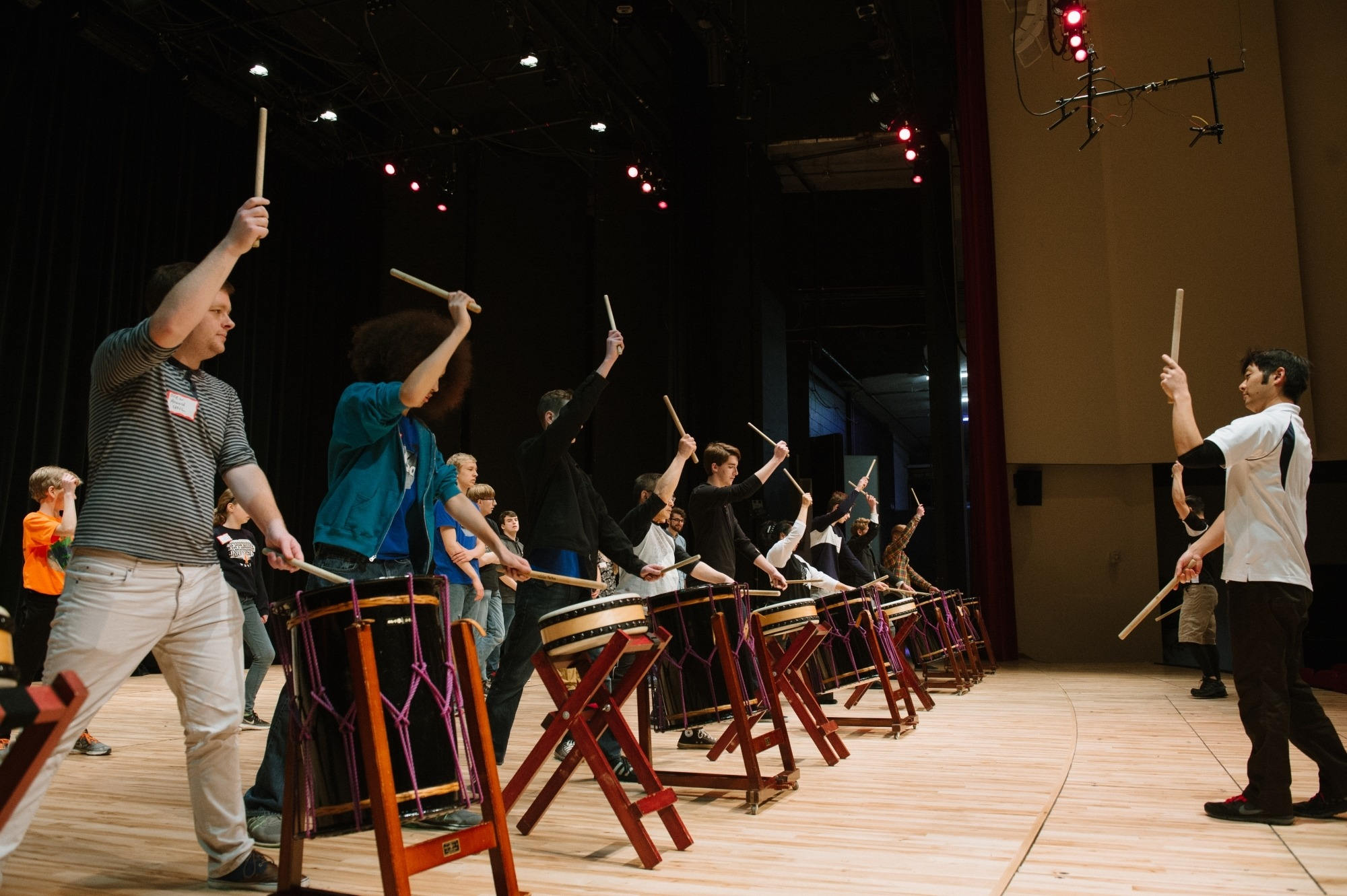 Image of a Taiko drummer leading community members in front of drums with right hands holding a drumstick in the air during a drumming master class